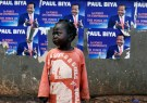A girl stands near a wall covered with Placards of Cameroon President Paul Biya, who runs for reelection scheduled for October 7, in Yaounde, Cameroon October 5, 2018. REUTERS/Zohra Bensemra - RC1BA30D24C0