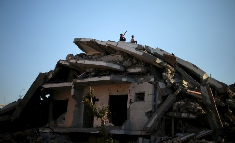 Palestinian boys sit atop the ruins of a house that witnesses said was destroyed by Israeli shelling during a 50-day war last summer, in the east of Gaza City May 12, 2015. REUTERS/Mohammed Salem       TPX IMAGES OF THE DAY      - GF10000092322