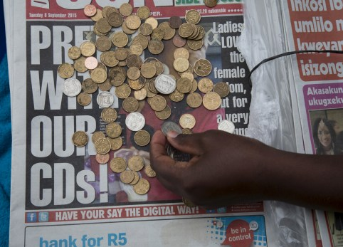 A newspaper vendor counts out change for a customer in Durban, September 8, 2015. South Africa's rand firmed more than 1 percent against the dollar, recovering from record lows in the previous session as bets on a rate hike in United States faded due to worries over global growth. The rand rose 1.04 percent to 13.8150 per dollar. REUTERS/Rogan Ward - GF10000197505