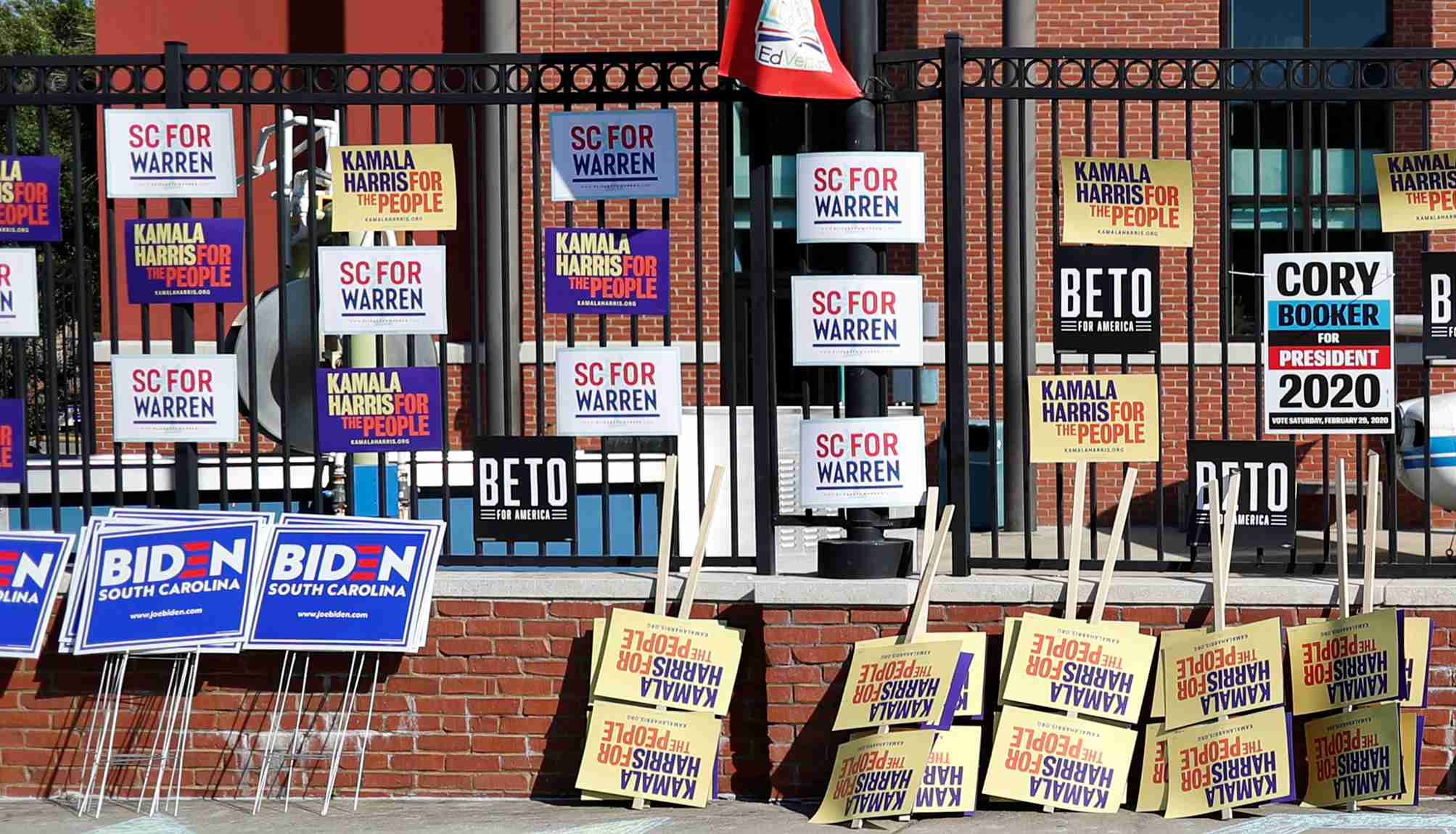 "A woman walks past a variety of campaign banners for Democratic presidential candidates at the entrance of ""Jim Clyburn's World Famous Fish Fry"" in Columbia, South Carolina, U.S., June 21, 2019.  REUTERS/Randall Hill - RC17A8C3A840"
