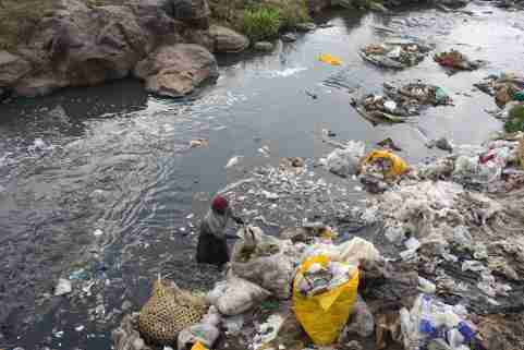 A woman recycles plastic bags from a river near the Dondora dumpsite close to the slum of Korogocho in the capital Nairobi, Kenya, March 17, 2015.