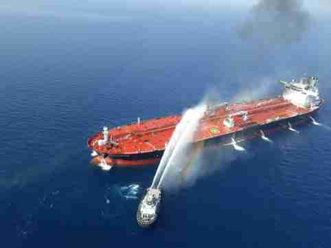 An Iranian navy boat tries to stop the fire of an oil tanker after it was attacked in the Gulf of Oman, June 13, 2019. Tasnim News Agency/Handout via REUTERS ATTENTION EDITORS - THIS IMAGE WAS PROVIDED BY A THIRD PARTY. - RC1D5E81AD00