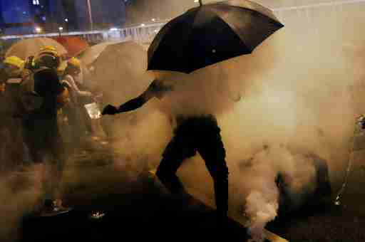 Pro-democracy protesters use umbrellas to protect themselves from tear gas during a protest against police violence during previous marches, near China's Liaison Office, Hong Kong, China July 28, 2019. REUTERS/Tyrone Siu - RC1304E1DFD0