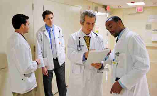 """Doctors Jordan Klein (2nd R) and Chane Price (R) confer as University of Miami interns Ignatios Papas (L) and Tim Sterrenberg (2nd L) look on in the Rehabilitation Unit of Jackson Memorial Hospital in Miami, September 30, 2013. The Obama administration accelerated its push to persuade individual Americans to sign up for the most extensive overhaul of the U.S. healthcare system in 50 years, the Affordable Care Act (commonly referred to as """"Obamacare"""") even as the program's foes in Congress fought to delay its launch with the threat of a federal government shutdown. The Jackson Health System is the largest in Florida and one of the largest in the U.S.  REUTERS/Joe Skipper (UNITED STATES - Tags: HEALTH) - RTR3FGCZ"""
