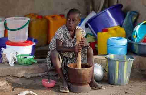 A girl displaced as a result of Boko Haram attacks in the northeast region of Nigeria, uses a mortar and pestle at a camp for internally displaced people in Yola, Adamawa State January 14, 2015. Boko Haram says it is building an Islamic state that will revive the glory days of northern Nigeria's medieval Muslim empires, but for those in its territory life is a litany of killings, kidnappings, hunger and economic collapse. Picture taken January 14. To match Insight NIGERIA-BOKOHARAM/     REUTERS/Afolabi Sotunde (NIGERIA - Tags: CIVIL UNREST SOCIETY EDUCATION) - GM1EB1K12UW01
