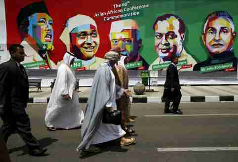 Delegates walk in front a poster of prominent attendees of the 1955 Asian-African Conference during a historical walk commemorating the 60-year anniversary of the Asian-African Summit, on Asia Afrika street in Bandung, Indonesia April 24, 2015. Leaders of Asian and African nations are in Jakarta to mark the 60th anniversary of a conference that made a developing-world stand against colonialism and led to the Cold War era's non-aligned movement.
