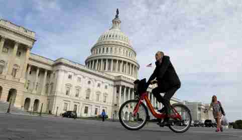 A cyclist passes the the U.S. Capitol, on the day the House is expected to vote here to repeal Obamacare in Washington, D.C., U.S., May 4, 2017. REUTERS/Kevin Lamarque - RC149622B020