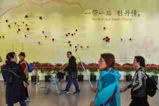 Visitors walk past a wall with a map showing the species of peony in Belt and Road Initiative (BRI) countries, at horticultural exhibition Beijing Expo 2019, in Beijing, China April 29, 2019. Picture taken April 29, 2019. REUTERS/Stringer ATTENTION EDITORS - THIS IMAGE WAS PROVIDED BY A THIRD PARTY. CHINA OUT. - RC1FBEBC8750