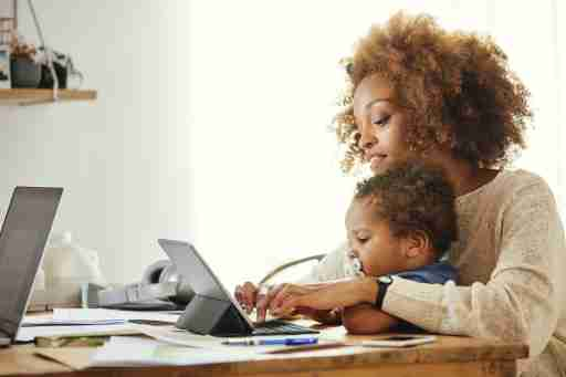 Woman typing on digital taMother using wireless computer while holding son at table.