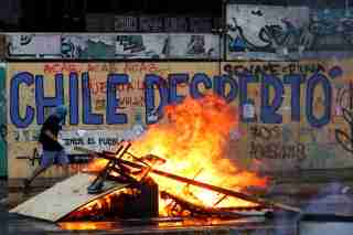"A demonstrator walks past a burning barricade during a protest against Chile's government in Santiago, Chile October 30, 2019. The graffiti on the wall reads: ""Chile woke up"". REUTERS/Jorge Silva - RC1AFD58CC70"