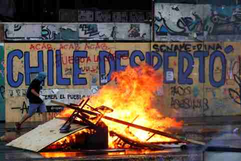 """A demonstrator walks past a burning barricade during a protest against Chile's government in Santiago, Chile October 30, 2019. The graffiti on the wall reads: """"Chile woke up"""". REUTERS/Jorge Silva - RC1AFD58CC70"""