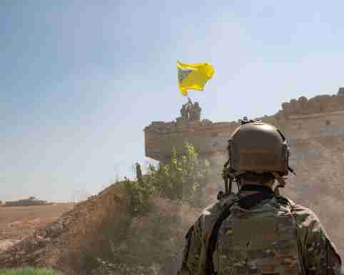 A U.S. soldier oversees members of the Syrian Democratic Forces as they demolish a YPG fortification and raise a Tal Abyad Military Council flag over the outpost as part of the security mechanism zone agreement, in Syria September 21, 2019.  Picture taken September 21, 2019.  U.S. Army/Staff Sgt. Andrew Goedl/Handout via REUTERS.  THIS IMAGE HAS BEEN SUPPLIED BY A THIRD PARTY. - RC1745C73700