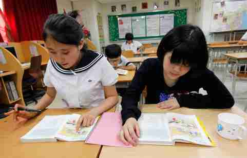 Lim Myeong-hee (L), 16, and her friend, middle school students who defected from North Korea, memorize English words as they look at English textbooks during supplementary lessons at the Hangyeore Middle and High School in Anseong, about 80 km (50 miles) south of Seoul, July 21, 2011. From the start of the 1950-53 Korean War till 1998, the total number of defectors in South Korea stood at less than 1,000. Today, the number is around 23,000. South Korean government last month started building a second reception centre for North Korean defectors at Hwacheon, about half an hour's drive from the border. Picture taken on July 21, 2011. To match feature KOREA-NORTH/DEFECTORS.  REUTERS/Jo Yong-Hak (SOUTH KOREA - Tags: POLITICS MILITARY EDUCATION) - GM1E78M1DEV01