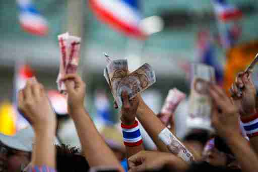 Anti-government protesters hold money to donate to protest leader Suthep Thaugsuban as he leads thousands of protesters in a march in central Bangkok January 19, 2014. Twenty-eight people were injured, seven of them seriously, in an explosion on Sunday at a camp of anti-government protesters in the center of the Thai capital, medical officials said. REUTERS/Athit Perawongmetha (THAILAND - Tags: POLITICS CIVIL UNREST) - GM1EA1J1C4C01