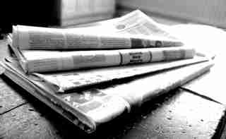 Black-and-white image of stacked newspapers