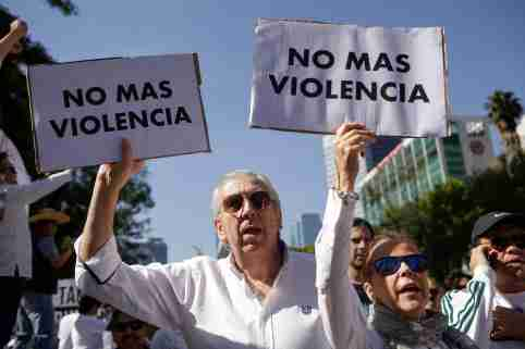 """Demonstrators hold up signs during a march to protest against violence on the first anniversary of President Andres Manuel Lopez Obrador taking office, in Mexico City, Mexico December 1, 2019. Signs read: """"No more violence"""". REUTERS/Jose Luis Gonzalez - RC2IMD9B6IC5"""