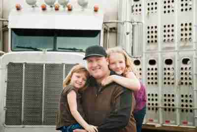 Cattle hauler truck driver and his daughters standing in front of his truck. It is raining.