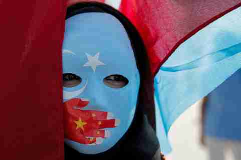 An ethnic Uighur demonstrator wears a mask as she attends a protest against China in front of the Chinese Consulate in Istanbul, Turkey, October 1, 2019. REUTERS/Huseyin Aldemir