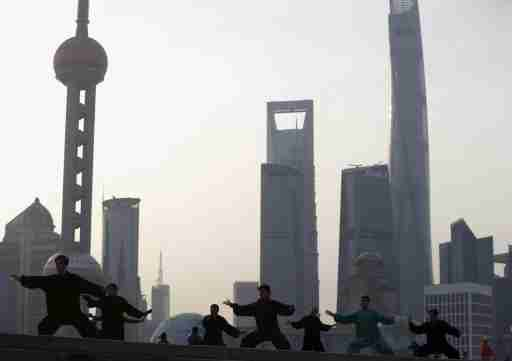 People perform Tai Chi on the Bund in front of the financial district of Pudong in Shanghai, China, March 25, 2016. REUTERS/Aly Song - GF10000359743