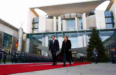 German Chancellor Angela Merkel and Libyan Prime Minister Fayez al-Sarraj walk during a welcome ceremony at the Chancellery in Berlin, Germany, December 7, 2017. REUTERS/Fabrizio Bensch - RC184FAC1510