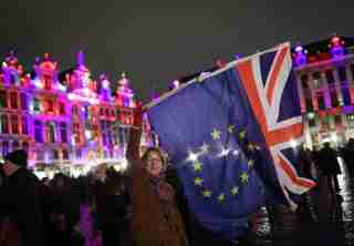 Deirdre Thomas, a resident of Belguim, waving an EU flag and a Union jack in Grand Place in Brussels, Belgium, during a celebration and farewell to the UK on the eve of Brexit.
