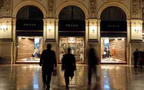 People walk past Prada's fashion store in downtown Milan February 4, 2015. The trend in luxury goods is to drum up same store sales by curbing expansion and wowing customers with new products, yet Prada continues to pay over the odds to open swanky new shops and stock them with handbags little changed from previous bestsellers. Prada, say analysts, now urgently needs to focus less on new stores and more on new handbags. Picture taken February 4. To match Analysis PRADA-STRATEGY/       REUTERS/Stefano Rellandini (ITALY - Tags: BUSINESS FASHION)