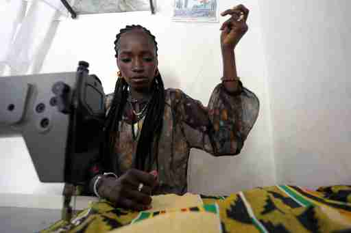 Fatou Kine works on a customer's order on a sewing machine purchased with money from the International Organization for Migration (IOM) in her shop in Guediawaye, Senegal April 16, 2018. Picture taken April 16, 2018.  To match Feature EUROPE-MIGRANTS/AFRICA   REUTERS/Mikal McAllister