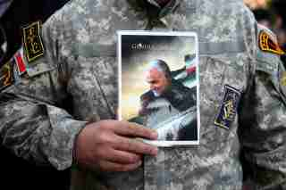 A demonstrator holds the picture of Qassem Soleimani during a protest against the assassination of the Iranian Major-General Qassem Soleimani, head of the elite Quds Force, and Iraqi militia commander Abu Mahdi al-Muhandis who were killed in an air strike in Baghdad airport, in Tehran, Iran January 3, 2020. WANA (West Asia News Agency)/Nazanin Tabatabaee via REUTERS ATTENTION EDITORS - THIS IMAGE HAS BEEN SUPPLIED BY A THIRD PARTY.     TPX IMAGES OF THE DAY