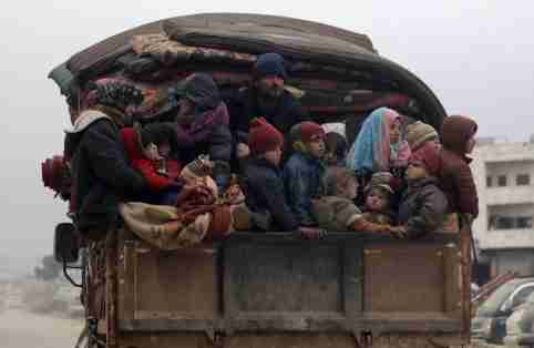 Internally displaced Syrians from western Aleppo countryside, ride on the back of a truck with belongings in Hazano near Idlib, Syria, February 11, 2020. REUTERS/Khalil Ashawi