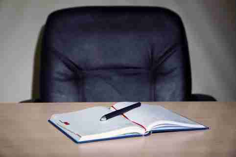 Empty office chair, notebook and pen
