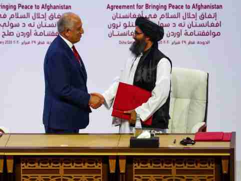 FILE PHOTO: Mullah Abdul Ghani Baradar, the leader of the Taliban delegation, and Zalmay Khalilzad, U.S. envoy for peace in Afghanistan, shake hands after signing an agreement at a ceremony between members of Afghanistan's Taliban and the U.S. in Doha, Qatar, February 29, 2020. REUTERS/Ibraheem al Omari/File Photo