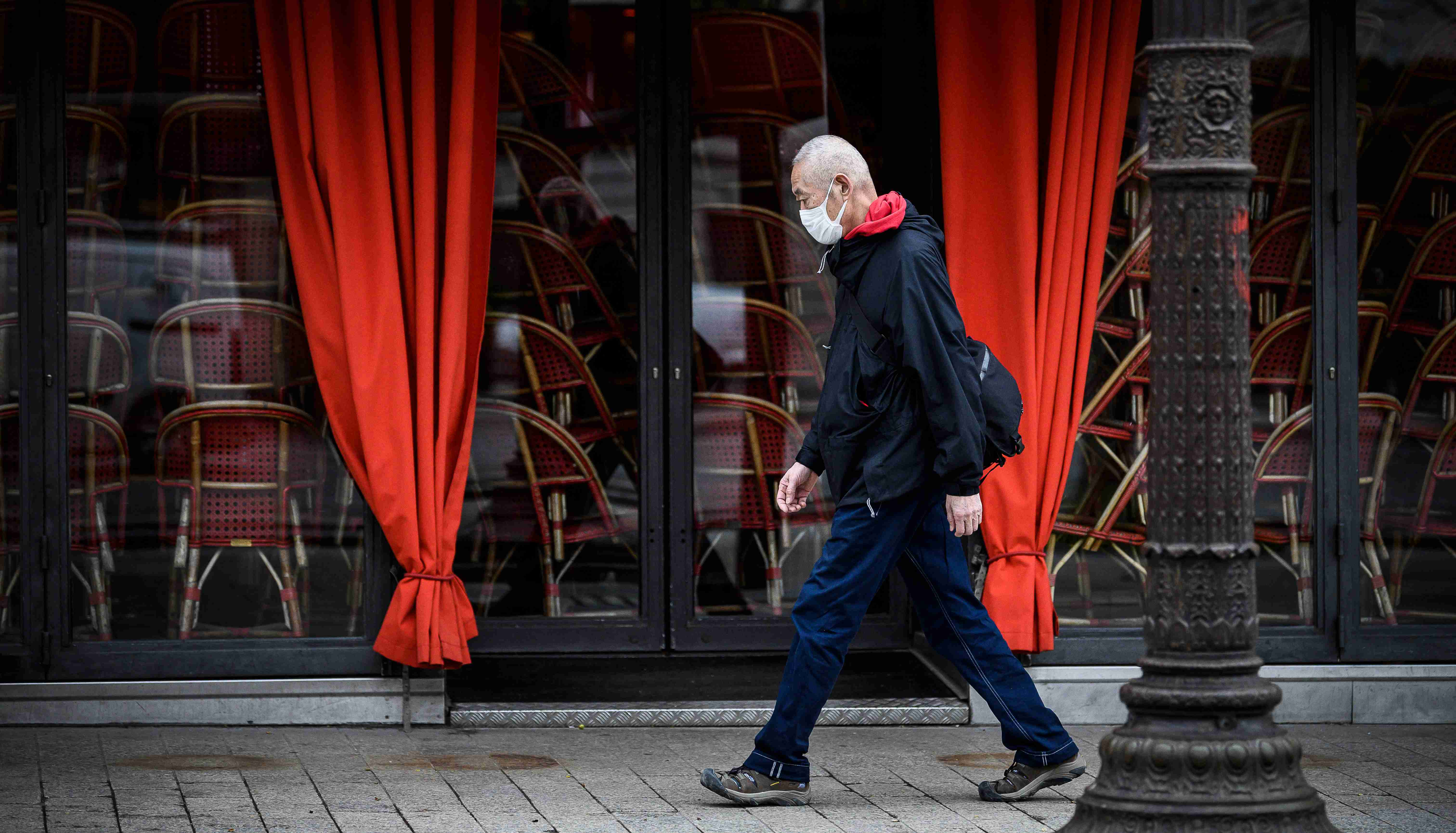 A man wearing a protective face mask in front of a restaurant in Paris (Avenue des Champs Elysee) as shops, schools remain closed and workers asked to work from home if possible, part of the latest French governmental measures against the coronavirus disease (COVID-19) outbreak, France, March 16, 2020.Photo by Eliot Blondet/ABACAPRESS.COM