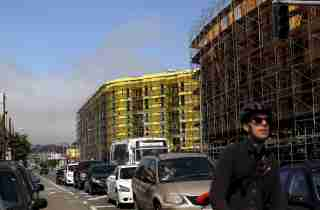 A bicyclist sits in traffic near a housing construction project in San Francisco, California June 2, 2015. The median rent for an apartment in the city is now $4,225 per month, according to local media. REUTERS/Robert Galbraith
