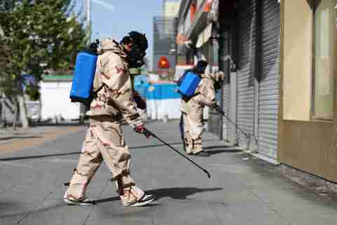 Volunteers from Basij forces wearing protective suits and face masks spray disinfectant in the streets, amid the coronavirus disease (COVID-19) fears, in Tehran, Iran April 3, 2020. WANA (West Asia News Agency)/Ali Khara via REUTERS ATTENTION EDITORS - THIS PICTURE WAS PROVIDED BY A THIRD PARTY