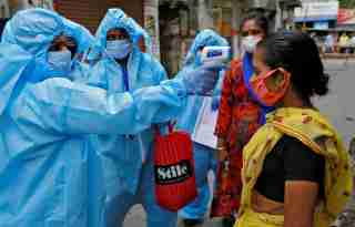 A health worker wearing protective gear uses an infrared thermometer to check the temperature of a woman during a door-to-door verification of people to find out if they have developed any coronavirus disease (COVID-19) symptoms, in a residential area in Kolkata, India, April 21, 2020. REUTERS/Rupak De Chowdhuri - RC2X8G92KBBP