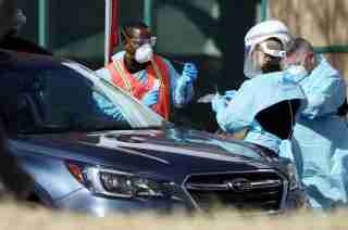 Health care workers test people at a drive-thru testing station run by the state health department, for people who suspect they have novel coronavirus, in Denver, Colorado, U.S. March 11, 2020. REUTERS/Jim Urquhart
