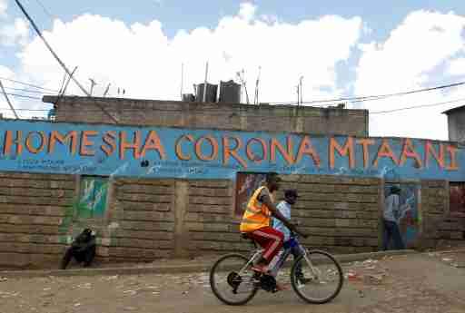 A man cycles past a wall mural advocating against the coronavirus disease (COVID-19) outbreak in Nairobi, Kenya April 11, 2020. REUTERS/Njeri Mwangi