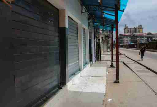 A man walks past closed shops in a nearly deserted wholesale market during lockdown by the authorities to limit the spread of coronavirus in Lagos, Nigeria, March 27, 2020. Picture taken March 27, 2020. REUTERS/Temilade Adelaja
