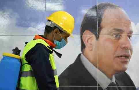 "A member of medical team is seen beside a banner for the Egyptian President Abdel Fattah el-Sisi, as he sprays disinfectant as a precautionary move amid concerns over the coronavirus disease (COVID-19) outbreak at the underground Al Shohadaa ""Martyrs"" metro station in Cairo, Egypt March 22, 2020. REUTERS/Mohamed Abd El Ghany"