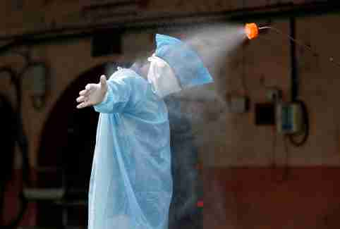 A municipal worker is sanitized after he cremated the body of a man, who died due to coronavirus disease (COVID-19), at a crematorium in Ahmedabad, India, April 22, 2020. REUTERS/Amit Dave - RC2R9G9CNWP2