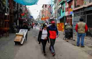 A couple wearing protective face masks walk along the Villa 31 slum, as the spread of the coronavirus disease (COVID-19) continues, in Buenos Aires, Argentina May 6, 2020. REUTERS/Agustin Marcarian
