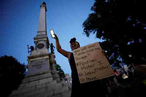 A protester speaks to the crowd underneath a Confederate monument during nationwide unrest following the death in Minneapolis police custody of George Floyd, in Raleigh, North Carolina, U.S. May 31, 2020. Picture taken May 31, 2020. REUTERS/Jonathan Drake     TPX IMAGES OF THE DAY