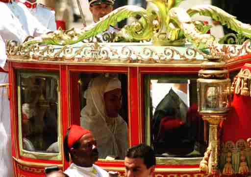 Morocco's new King Mohammed VI sits in a horse-drawn red carriage, on his way to preside over his first Moslem prayers at the Ahl Fez Mosque July 30, since taking the throne last week. According to tradition, the first Friday (after being crowned) the king presides over prayers as a symbol that the king is carrying out his role as the Commander of the Faithful.JB/AA