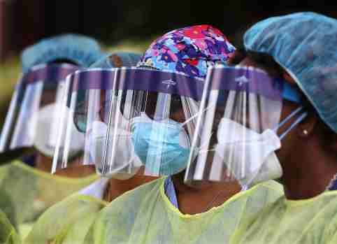 Some of the more than two dozen specimen collection volunteers line up to begin taking hundreds of free COVID-19 tests at a pop-up site at the House of Hope on Monday, May 4, in Decatur, Ga. Pastors, local physicians, health ministers, and other community leaders united to encourage area residents to get tested. (Curtis Compton/Atlanta Journal-Constitution/TNS)
