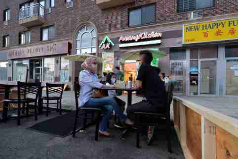 Wearing masks in the time of COVID-19, the Sukarmadijaya family sit dine al fresco at a table set up off the sidewalk in front of Awang Kitchen, an Indonesian restaurant along Queens Boulevard, in the Elmhurst section of Queens, NY, June 26, 2020. Under Phase II, restaurants may serve customers at sidewalk tables and 8ft into the street from sidewalk, all meant to prevent the further spread of COVID-19 pandemic. (Anthony Behar/Sipa USA)No Use UK. No Use Germany.