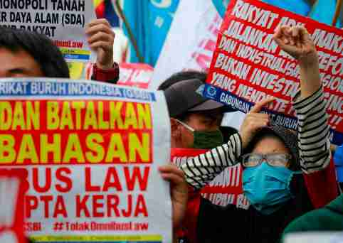 """Members of Indonesian labor organizations protest outside the Indonesian Parliament against the cancellation of an """"omnibus bill"""" that aims to revise dozens of existing laws in order to ease the way for investment in Southeast Asia's largest economy in Jakarta, Indonesia, July 16, 2020. REUTERS/Ajeng Dinar Ulfiana"""
