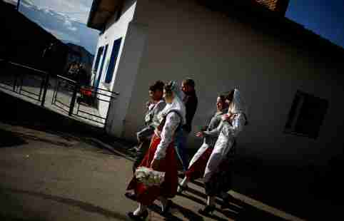 Bulgarian Muslims Mehmed Aiumankov (L), and his bride Fatme Kichukova (2nd L) walk with their friends during their wedding ceremony in the village of Ribnovo, in the Rhodope Mountains, some 210 km (130 miles) south of Sofia December 11, 2011. The remote mountain village of Ribnovo in southwest Bulgaria has kept its traditional winter marriage ceremony alive despite decades of Communist persecution, followed by poverty that forced many men to seek work abroad. The wedding ritual was resurrected with vigour among the Pomaks - Slavs who converted to Islam under Ottoman rule. Today Muslims make up 10 percent of Bulgaria's 7.4 million population. The highlight of the ceremony is the painting of the bride's face, where in a private rite open only to female in-laws, her face is covered in thick, chalky white paint and decorated with colourful sequins. Picture taken December 11, 2011. REUTERS/Stoyan Nenov (BULGARIA - Tags: SOCIETY RELIGION)