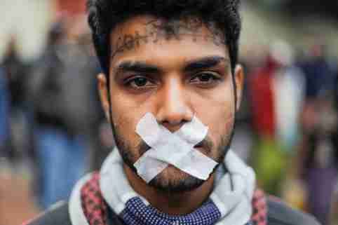A protester with tapes over his mouth attends a protest against a new citizenship law in Delhi, India, December 19, 2019. REUTERS/Adnan Abidi