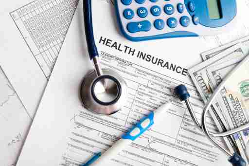 A pile of health insurance documents, medical equipment, and money.
