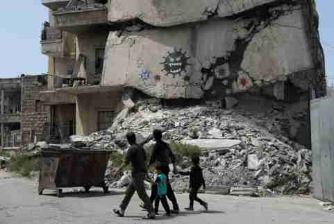 People walk past a damaged building depicting drawings alluding to the coronavirus and encouraging people to stay at home, in the rebel-held Idlib city, amid concerns about the spread of the coronavirus disease (COVID-19), Syria April 18, 2020. REUTERS/Khalil Ashawi     TPX IMAGES OF THE DAY
